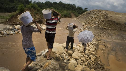 Chinese gold miners carry buckets of gold-laden heavy silt to be processed at a different facility from a gold mining site near Laiza, Kachin State, Myanmar.