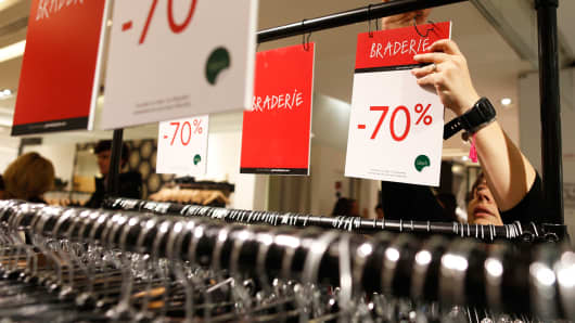 An employee adjusts a discount sign in a department store in Paris, January 6, 2015.