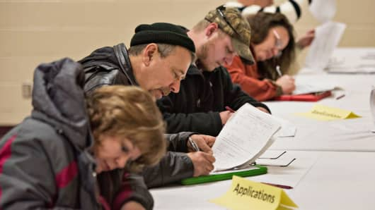 Job seekers fill out applications during a job fair in Princeton, Illinois, Jan. 5, 2015.