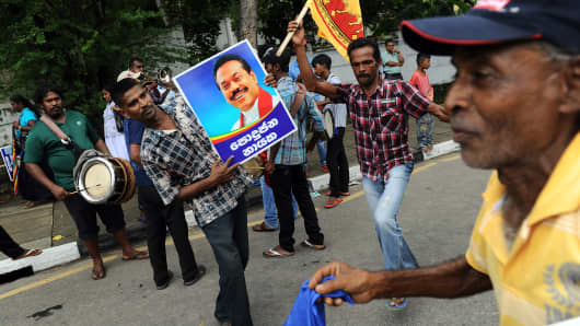 Supporters of Sri Lankan President Mahinda Rajapaksa dance while holding a poster bearing his image outside the election office in Colombo.