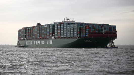 Tug boats greet the CSCL Globe as it arrives at the Port of Felixstowe