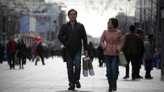 Shoppers walking along a street in Beijing.