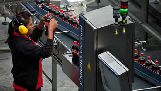 An attendant checks bottles on a production line at the Coca-Cola bottling plant in Nilai on the outskirts of Kuala Lumpur on November 3, 2014.