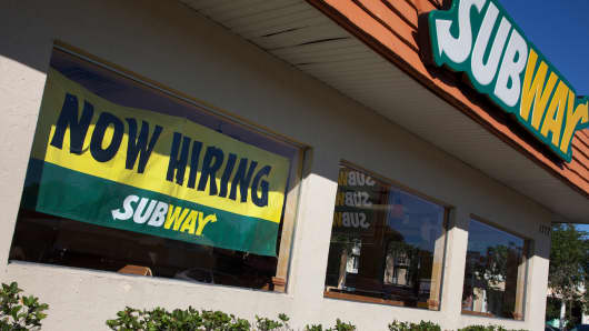 "A ""now hiring"" sign in the window of a Subway restaurant in Sarasota, Fla."
