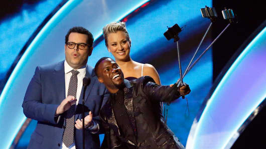 Actors Kevin Hart, center, Josh Gad and Kaley Cuoco, take selfies on the stage during the 2015 People's Choice Awards in Los Angeles, Jan. 7, 2015.