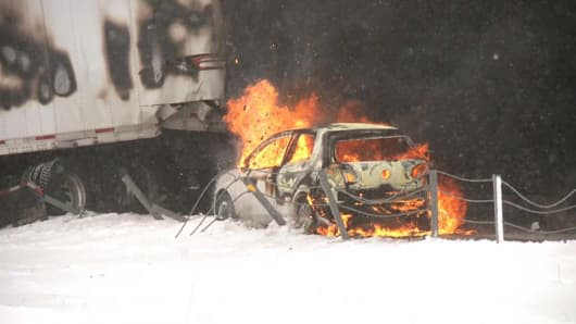 A car is on fire after a 40-vehicle pileup on I-94 between Battle Creek and Galesburg, Mich., Jan. 9, 2015.