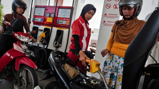 A station attendant refuels a moped at a fuel station on April 30, 2013 in Yogyakarta, Indonesia.