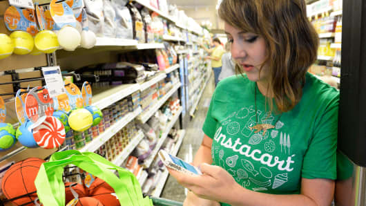 A shopper for Instacart studies her smart phone as she shops for a customer at Whole Foods in Denver.