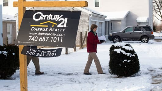A real estate agent exits a home for sale in Lancaster, Ohio, Jan. 9, 2015.