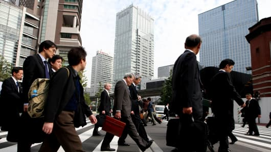 Japanese business men walk along the street in Tokyo, Japan.