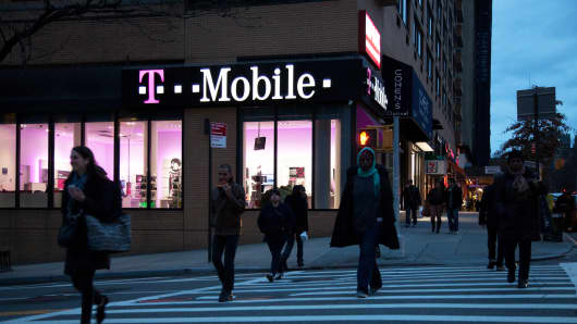 Pedestrians pass in front of a T-Mobile location in New York.