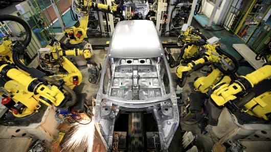 Robot assembler work on cars during the assembly process at Nissan Motor Company's Kyushu Plant on November 23, 2007 in Kiyakyushu, Japan.