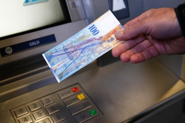 A man holds a 100 Swiss franc bank note in front of an ATM in Bern.
