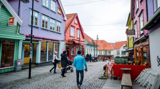 Pedestrians walk in the old town district of Stavanger, Norway.