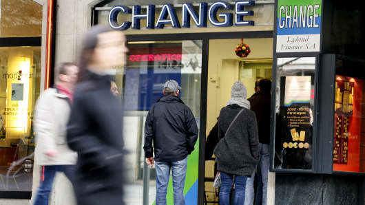People queue outside a currency exchange office in Geneva, January 15, 2015. The Swiss National Bank scrapped its cap on the franc on Thursday sending the safe-haven currency crashing below the 1.20 per euro floor it set over three years ago.