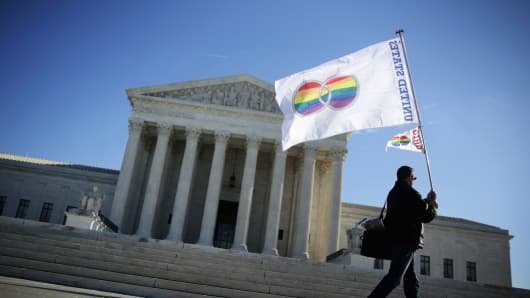 A person with Equality Beyond Gender holds a 'marriage pride flag' outside the U.S. Supreme Court, January 9, 2015 in Washington.