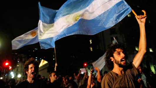 Demonstrators shout slogans as they wave Argentine flags during a protest over the death of prosecutor Alberto Nisman, outside the Casa Rosada Presidential Palace in Buenos Aires January 19, 2015.