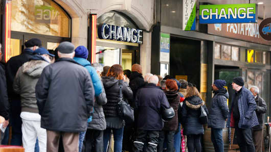 People queue outside a currency exchange office in Geneva, January 16, 2015.