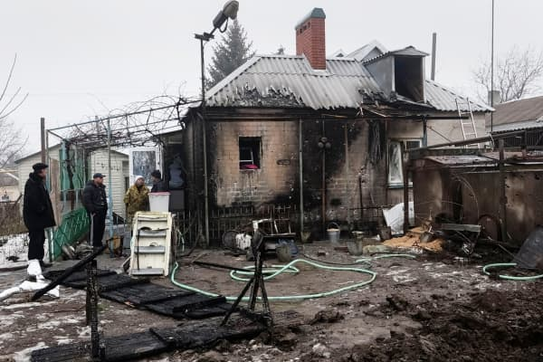 Local residents inspect their home, which was damaged by last night's shelling in the village of Sartan, near Mariupol January 20, 2015.