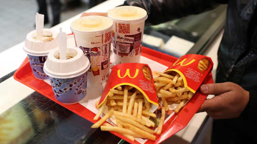 A customer collects a tray of french fries, cold drinks and McFlurry deserts from the service counter inside a McDonald's Corp. fast food restaurant.