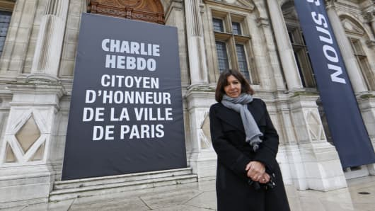 "Paris Mayor Anne Hidalgo poses near a banner which reads ""Charlie Hebdo, Honorary citizen of Paris,"" displayed in front of the City Hall."