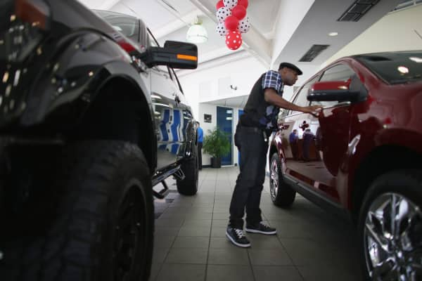 A customer ooks at a Ford vehicle on the showroom floor at a Ford AutoNation car dealership in North Miami, Florida.