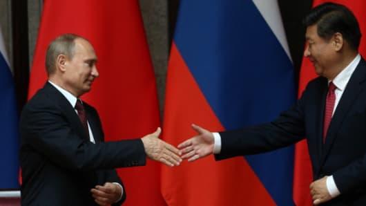 Russian President Vladimir Putin (L) greets Chinese President Xi Jinping