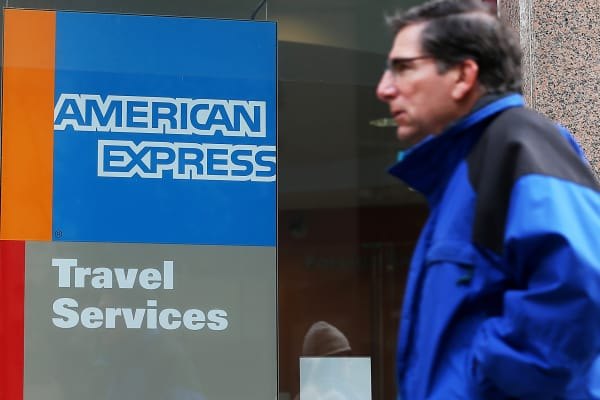 Man walking past American Express Travel Services office