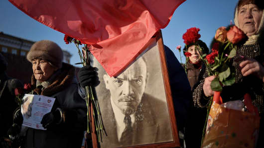 Russian communist party supporters carry a portrait of late Soviet leader Vladimir Lenin as they take part in a memorial ceremony to mark the 91st anniversary of his death, in Moscow's Red Square, Jan. 21, 2015.