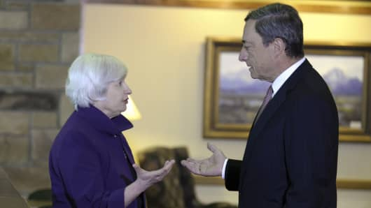 Janet Yellen, chair of the U.S. Federal Reserve, left, speaks with Mario Draghi, president of the European Central Bank during the Jackson Hole economic symposium on Aug. 22, 2014.
