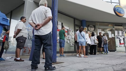 Job seekers wait in a line to enter an employment center before opening in Athens, Greece, Sept. 10, 2014.