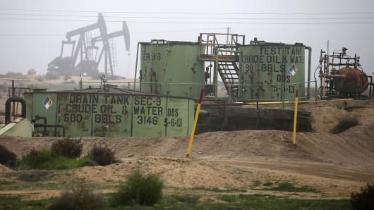 Oil tanks and pump jacks are seen in an oil field near Bakersfield, Calif.