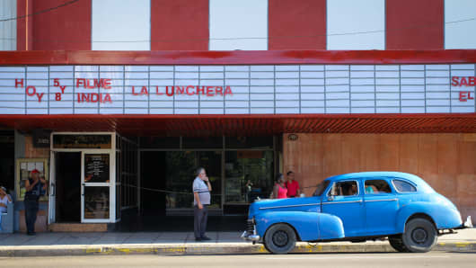 A classic car sits outside a movie theater in Havana, Cuba.