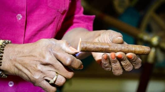 A woman lights a hand-rolled cigar.