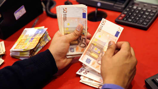An employee counts 50-euro banknotes at his desk inside a Travelex store, operated by Travelex Holdings in London.