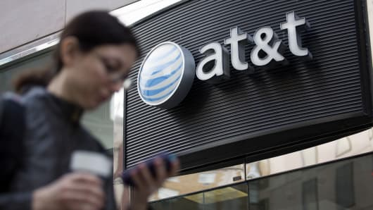 A pedestrian looks at a mobile phone while walking past an AT&T store in Washington, D.C.