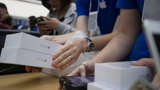 Boxes of iPhone 6 smartphones sit stacked on a table as customers make a purchase during the sales launch at the Apple Inc. store in Palo Alto, Calif.