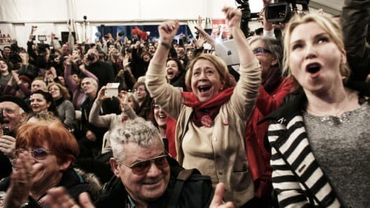 Supporters of the opposition radical leftist Syriza party cheer at exit poll results which indicate that Syriza have a clear lead in Athens, Greece.