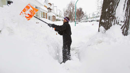 Man shoveling show following a snow storm in Buffalo last November.