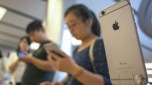 Customers browse iPhone 6s smartphones at an Apple Store in Shanghai.