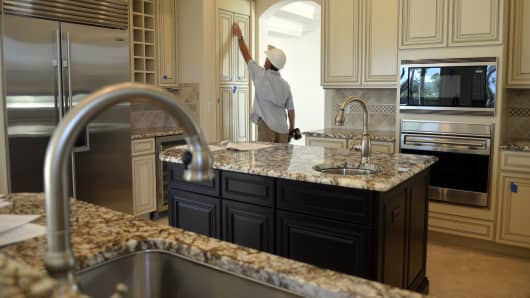 A cabinet specialist adjusts doors on a pantry of a Tresana model home at Toll Brothers Homes' Jupiter Country Club housing development in Jupiter, Florida.