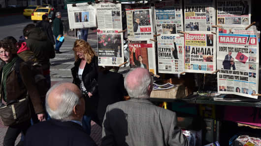 People read newspaper headlines in Athens, January 26, 2015.
