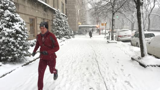 A runner runs down 5th Ave Ave as a blizzard hits New York.