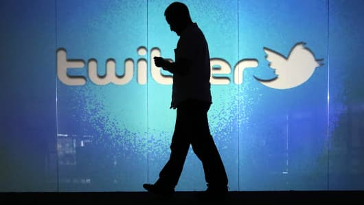 Silhouette of man against Twitter logo