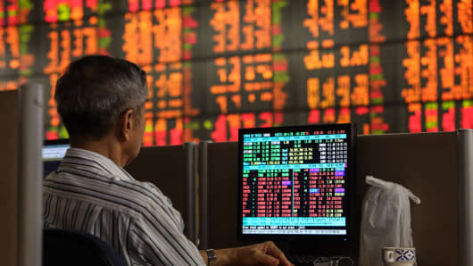 A customer checks market movements on a computer as an electronic board displays stock prices at the Asia Plus Securities headquarters in Bangkok, Thailand.
