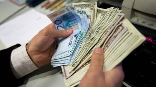 An employee counts euros and U.S. dollar notes in a currency exchange store in Lisbon, Portugal.