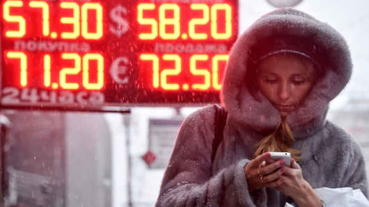 A woman walks past a board listing foreign currency rates against the Russian ruble outside an exchange office in central Moscow