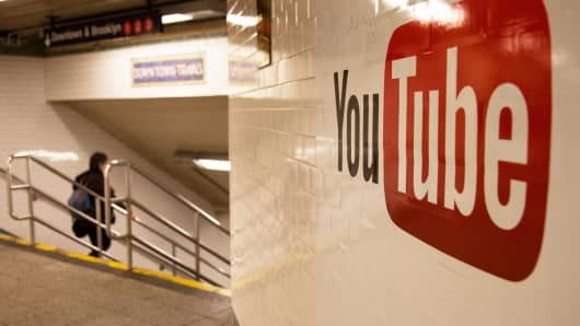 Pedestrians walk past YouTube advertising in the New York subway