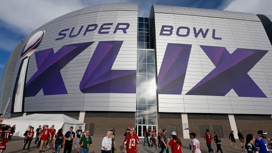 Fans walk outside University of Phoenix Stadium in Glendale, Ariz., Jan. 25, 2015, ahead of Super Bowl XLIX.