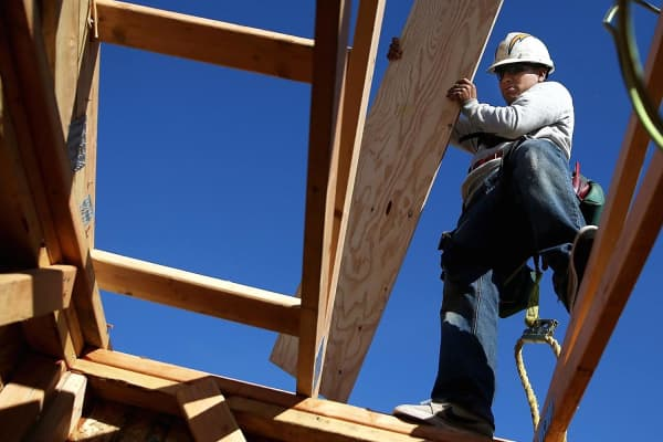 A worker carries lumber as he builds a new home in Petaluma, California.